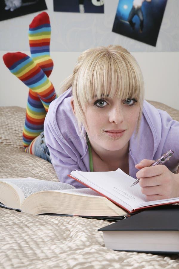Όμορφη γυναίκα σπουδαστής που γράφει στο βιβλίο στο κρεβάτι στοκ εικόνες