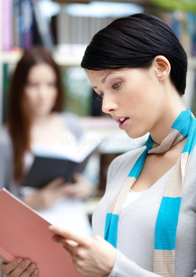 Όμορφη γυναίκα σπουδαστής στη βιβλιοθήκη ενάντια στα ράφια στοκ εικόνες