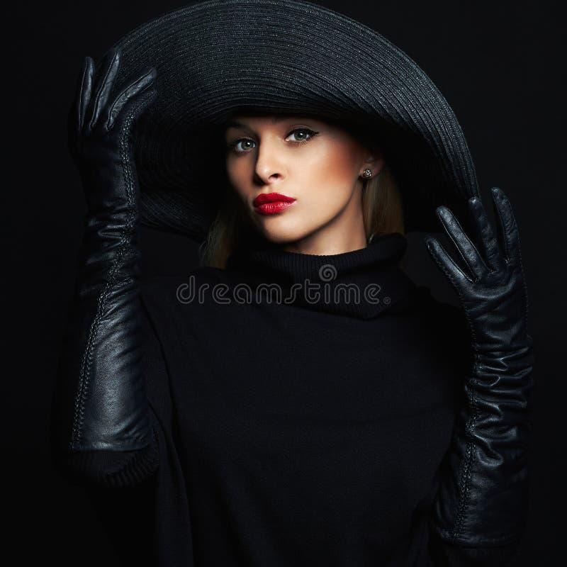 Όμορφη γυναίκα στα γάντια καπέλων και δέρματος στοκ εικόνες