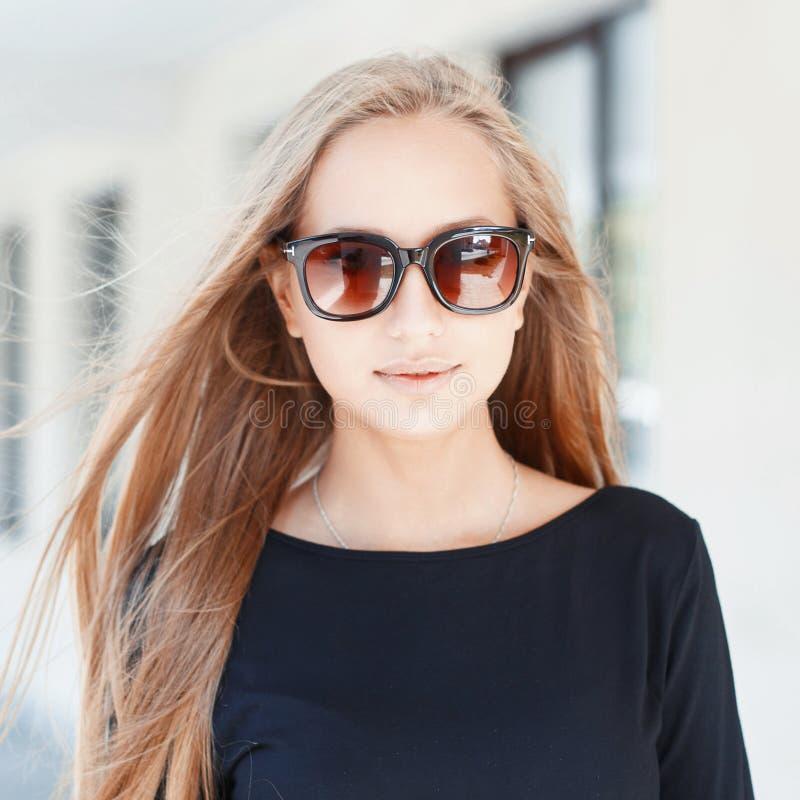 Όμορφη γυναίκα στα γυαλιά ηλίου στο υπόβαθρο των παραθύρων Σε ένα ηλιόλουστο δ στοκ φωτογραφία