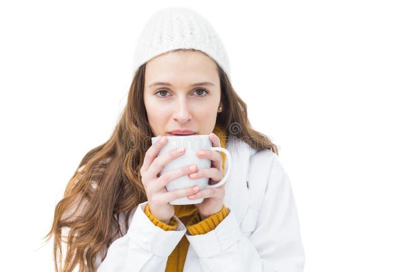 Όμορφη γυναίκα στα χειμερινά ενδύματα που πίνει ένα καυτό ποτό στοκ εικόνες