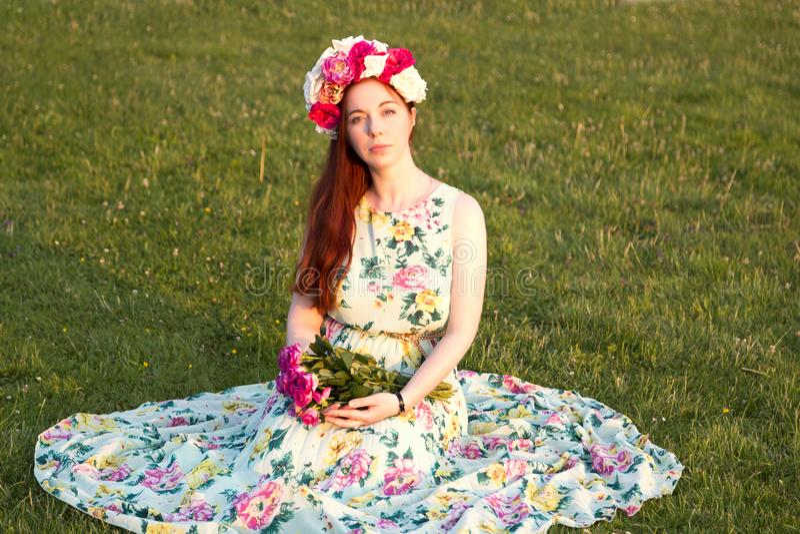Όμορφη γυναίκα στα floral λουλούδια εκμετάλλευσης στεφανιών στοκ φωτογραφία με δικαίωμα ελεύθερης χρήσης