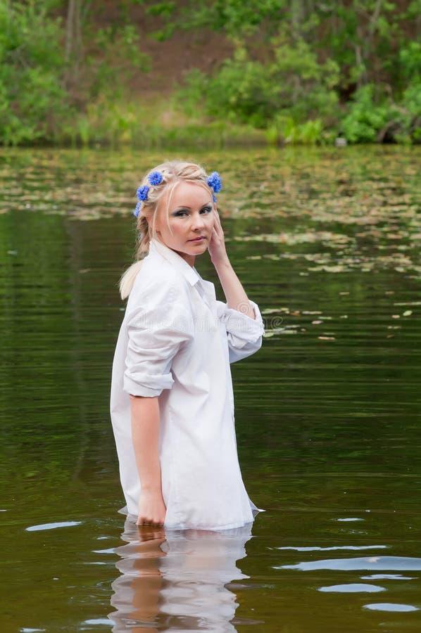 Όμορφη γυναίκα στην άσπρη στάση στη λίμνη στοκ φωτογραφίες