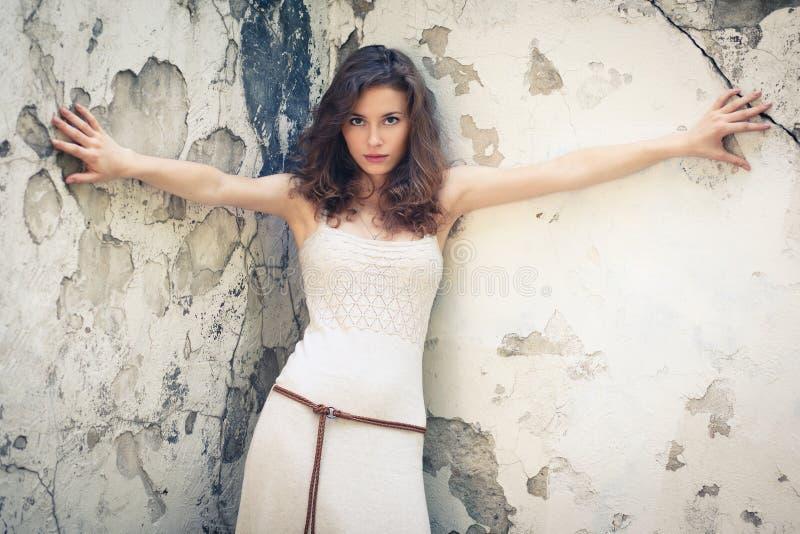 Όμορφη γυναίκα στην ανασκόπηση του παλαιού τοίχου στοκ εικόνα