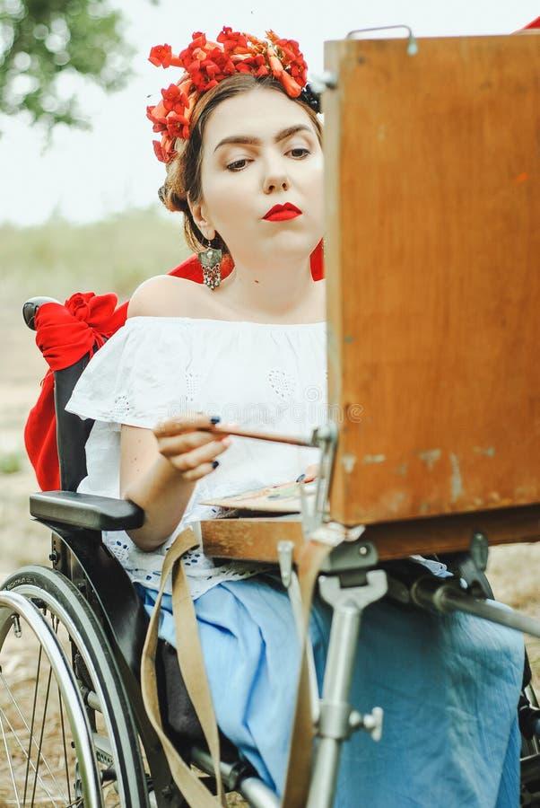 Όμορφη γυναίκα στην καρέκλα ροδών, ζωγραφική Υπαίθρια περίοδος επικοινωνίας στοκ εικόνες