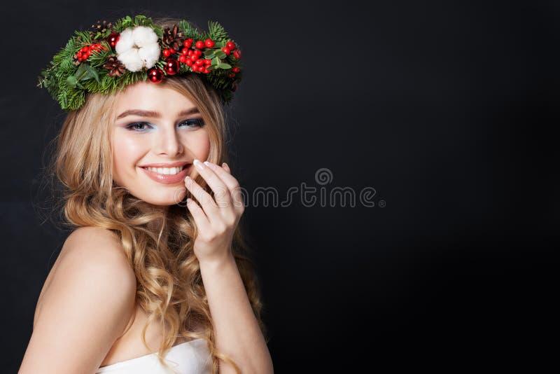 Όμορφη γυναίκα στην πράσινη κορώνα έλατου στο σκοτεινό υπόβαθρο Ευτυχές κορίτσι με το ξανθό στεφάνι τρίχας και Χριστουγέννων στοκ εικόνες με δικαίωμα ελεύθερης χρήσης