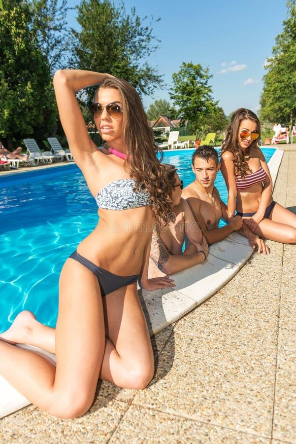 Όμορφη γυναίκα στην τοποθέτηση μπικινιών στην άκρη της πισίνας πίσω από τους φίλους της στοκ φωτογραφία με δικαίωμα ελεύθερης χρήσης