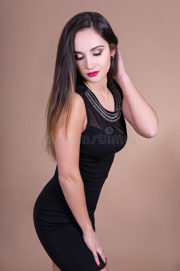 Όμορφη γυναίκα στη μαύρη τοποθέτηση φορεμάτων πέρα από το μπεζ υπόβαθρο στοκ εικόνες με δικαίωμα ελεύθερης χρήσης