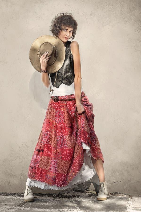 Όμορφη γυναίκα στη μοντέρνη μακριά φούστα με το καπέλο κάουμποϋ στοκ εικόνες