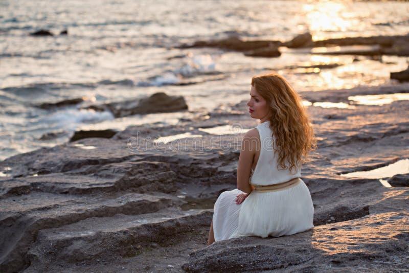 Όμορφη γυναίκα στο άσπρο φόρεμα που απολαμβάνει το ηλιοβασίλεμα στοκ εικόνα