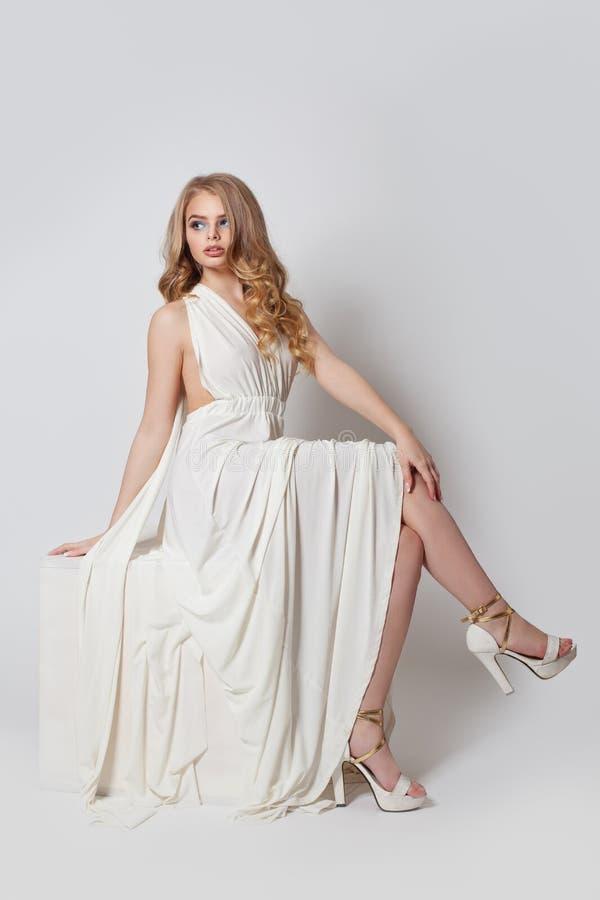 Όμορφη γυναίκα στο άσπρο φόρεμα Όμορφο πρότυπο με τα τέλεια πόδια στα υψηλά τακούνια στοκ εικόνες