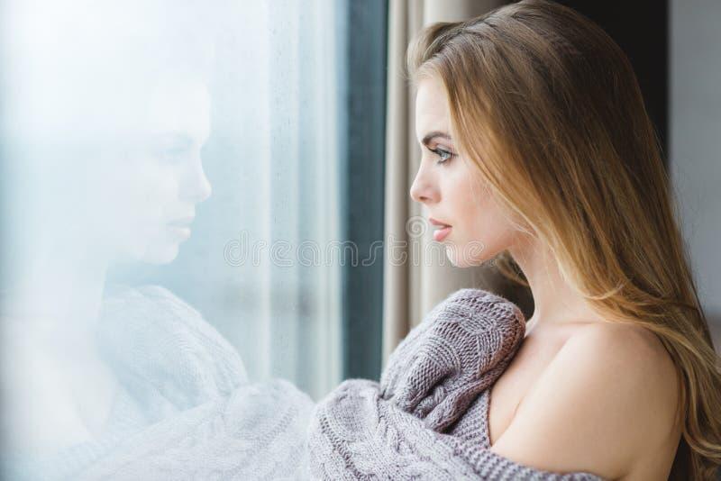 Όμορφη γυναίκα στο γκρίζο πλεκτό coverlet που κοιτάζει από το παράθυρο στοκ εικόνα με δικαίωμα ελεύθερης χρήσης
