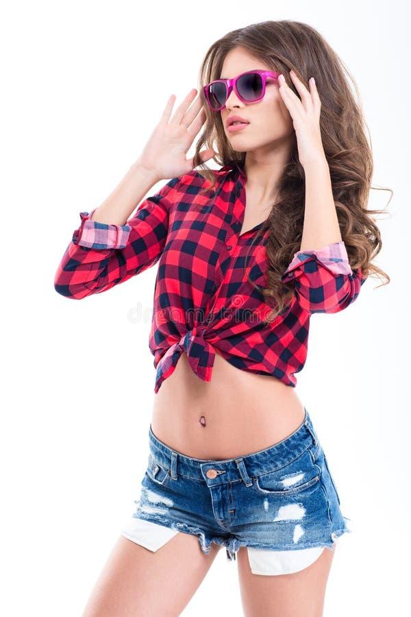Όμορφη γυναίκα στο ελεγμένο πουκάμισο, τα σορτς τζιν και τα ρόδινα γυαλιά ηλίου στοκ εικόνα