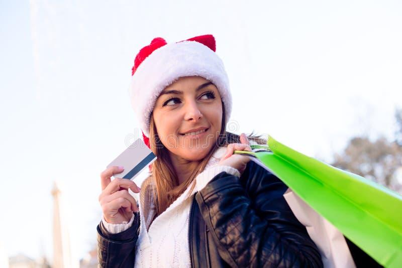 Όμορφη γυναίκα στο καπέλο Santa με την τσάντα αγορών και την πιστωτική κάρτα στοκ φωτογραφία