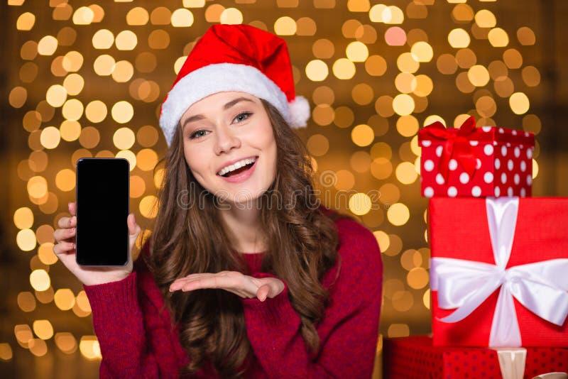 Όμορφη γυναίκα στο καπέλο santa που παρουσιάζει στο τηλέφωνο κυττάρων κενή οθόνη στοκ φωτογραφία με δικαίωμα ελεύθερης χρήσης