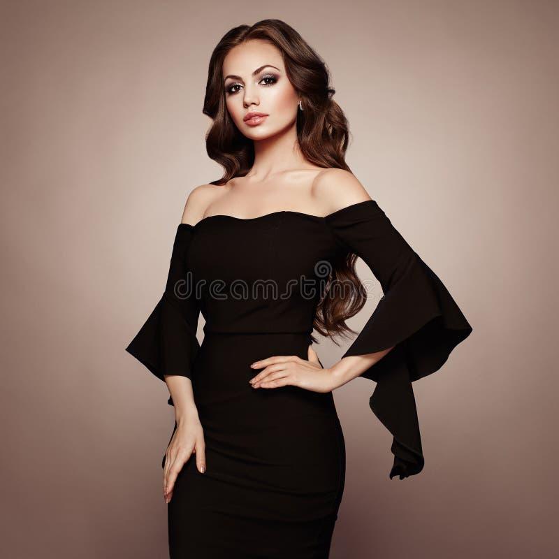 Όμορφη γυναίκα στο κομψό μαύρο φόρεμα βραδιού στοκ εικόνες