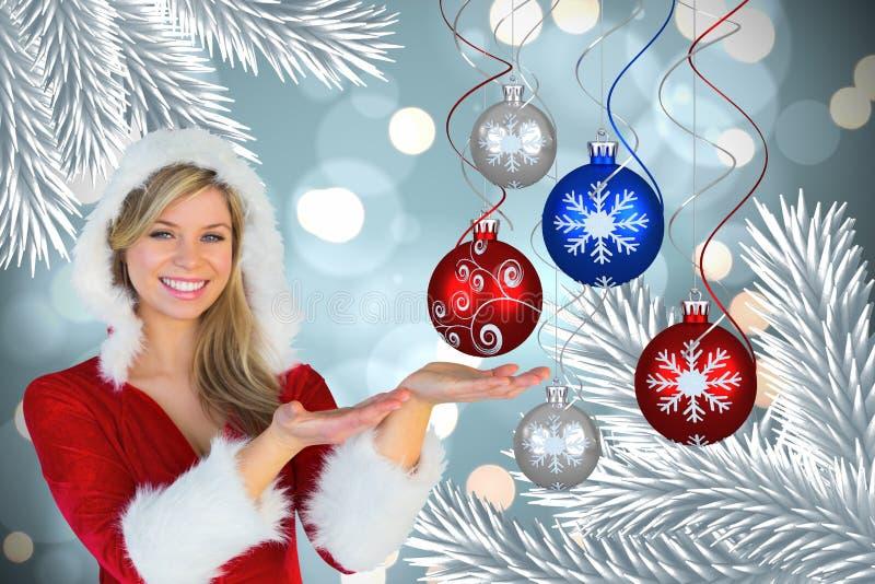 Όμορφη γυναίκα στο κοστούμι santa που παρουσιάζει μπιχλιμπίδι Χριστουγέννων στοκ φωτογραφίες με δικαίωμα ελεύθερης χρήσης