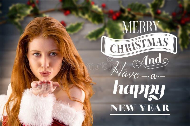 Όμορφη γυναίκα στο κοστούμι santa που φυσά ένα φιλί με τους χαιρετισμούς Χριστουγέννων στοκ εικόνα
