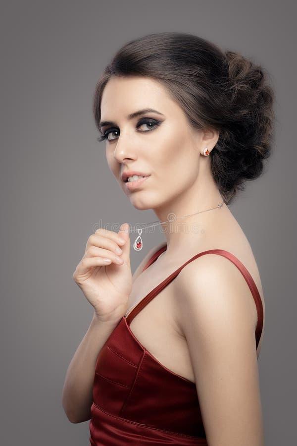 Όμορφη γυναίκα στο κόκκινο κομψό φόρεμα που φορά το ροδοκόκκινο κόσμημα στοκ εικόνα με δικαίωμα ελεύθερης χρήσης