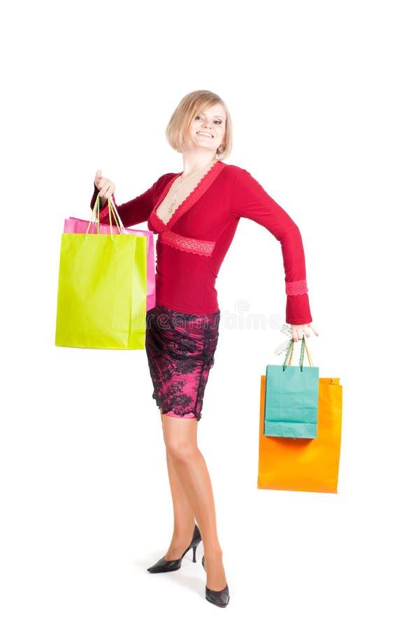 Όμορφη γυναίκα στο κόκκινο με τις τσάντες αγορών στοκ φωτογραφίες με δικαίωμα ελεύθερης χρήσης