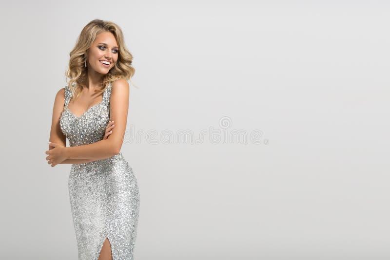 Όμορφη γυναίκα στο λάμποντας ασημένιο φόρεμα στοκ εικόνες