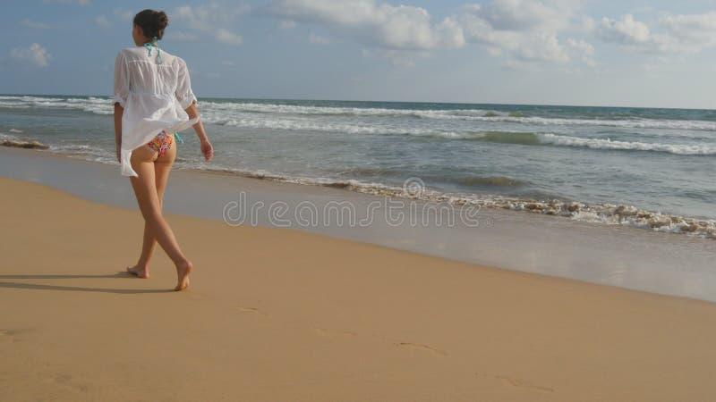 Όμορφη γυναίκα στο μαγιό και πουκάμισο που περπατά στην παραλία θάλασσας χωρίς παπούτσια Νέο κορίτσι που πηγαίνει στην ωκεάνια ακ στοκ εικόνες