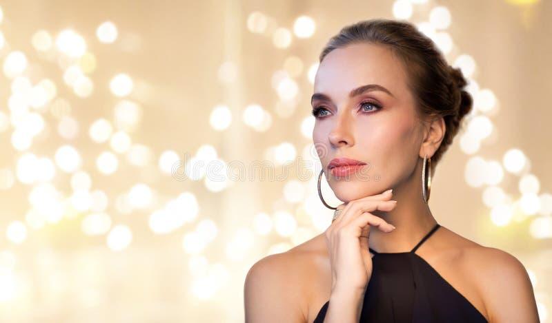 Όμορφη γυναίκα στο μαύρο κόσμημα διαμαντιών φθοράς στοκ εικόνα