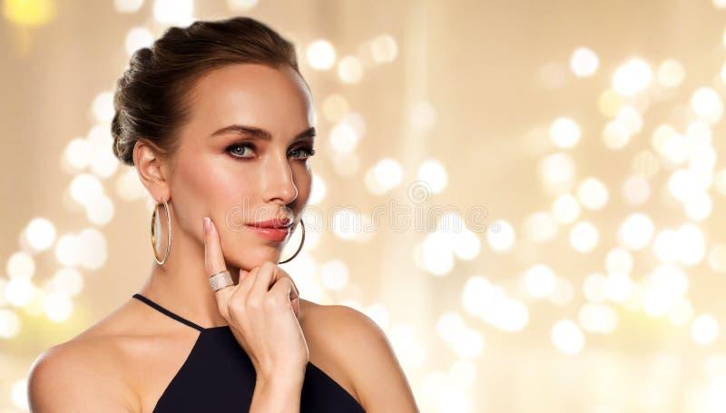 Όμορφη γυναίκα στο μαύρο κόσμημα διαμαντιών φθοράς στοκ φωτογραφία