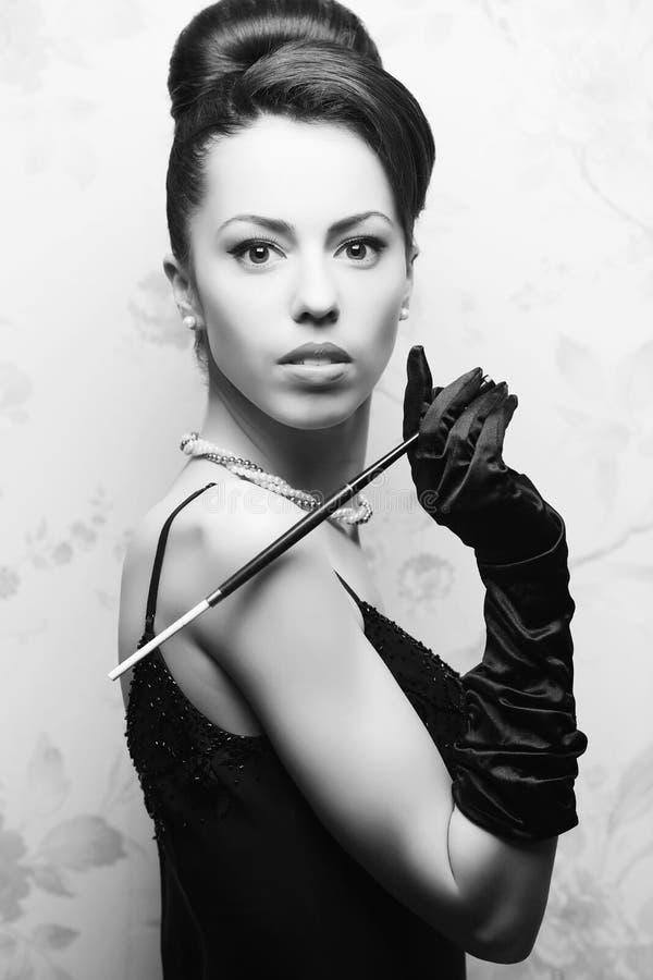 Όμορφη γυναίκα στο μεγάλο κάπνισμα φορεμάτων κοκτέιλ στοκ εικόνα