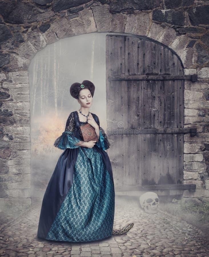 Όμορφη γυναίκα στο μεσαιωνικό φόρεμα με το βιβλίο στοκ φωτογραφίες