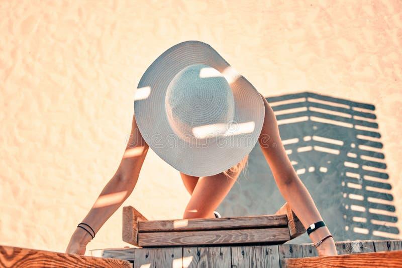 Όμορφη γυναίκα στο μπικίνι που αναρριχείται στο σταθμό lifeguard, lifeguard πύργος στοκ εικόνα με δικαίωμα ελεύθερης χρήσης