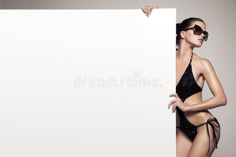 Όμορφη γυναίκα στο μπικίνι που κρατά το μεγάλο κενό άσπρο πίνακα διαφημίσεων στοκ φωτογραφίες με δικαίωμα ελεύθερης χρήσης