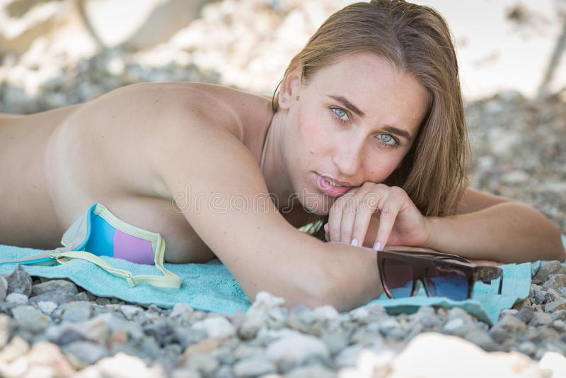 Όμορφη γυναίκα στο μπικίνι που στηρίζεται στην παραλία χαλικιών στοκ φωτογραφίες