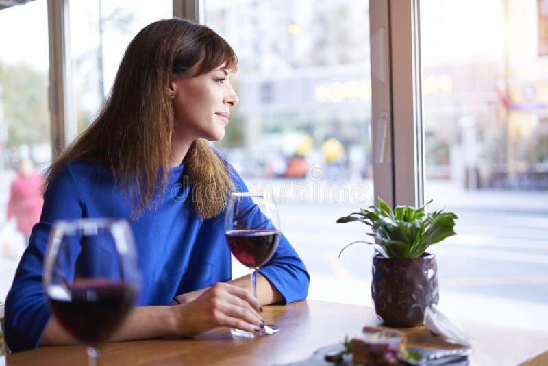 Όμορφη γυναίκα στο μπλε φόρεμα που πίνει το κόκκινο κρασί κοντά στο παράθυρο στον καφέ, καταψύχοντας στις διακοπές ή τις διακοπές στοκ φωτογραφία με δικαίωμα ελεύθερης χρήσης