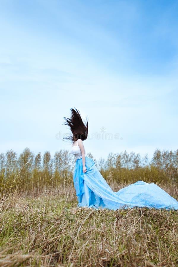 Όμορφη γυναίκα στο μπλε μακρύ φόρεμα με το πετώντας ύφασμα στοκ εικόνες