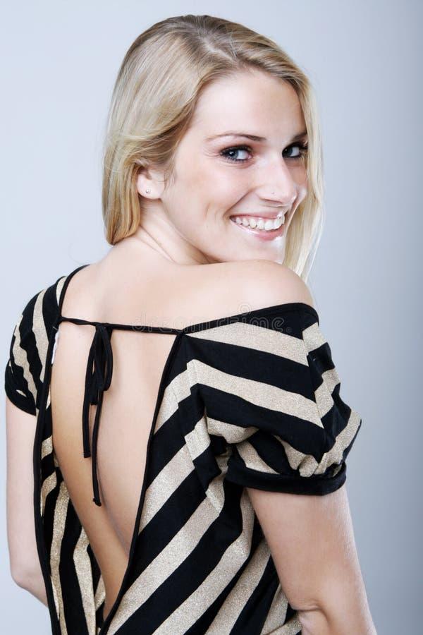 Όμορφη γυναίκα στο πουκάμισο Backless που χαμογελά στη κάμερα στοκ εικόνες