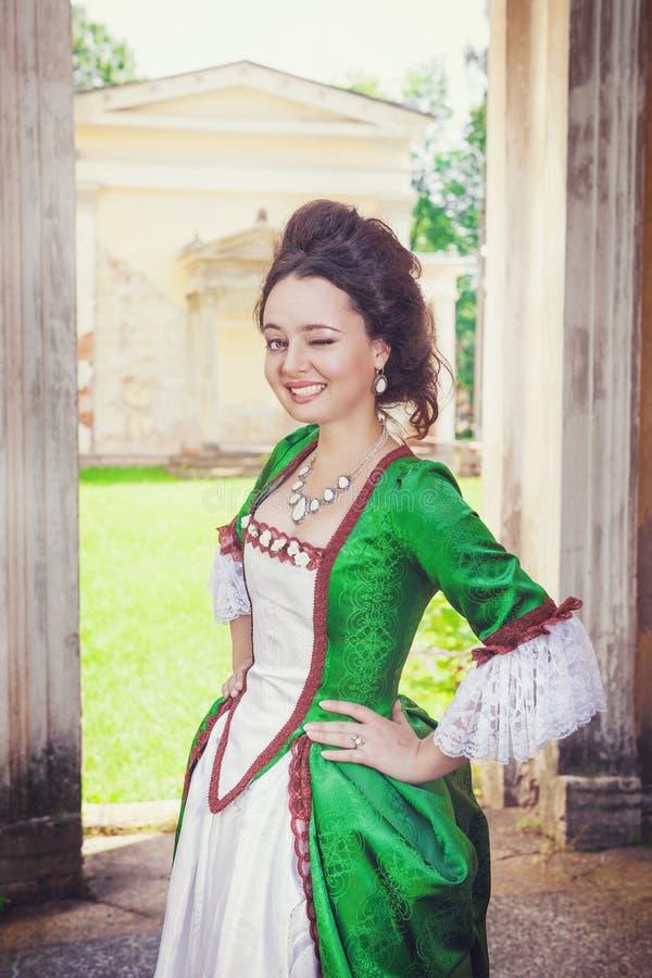Όμορφη γυναίκα στο πράσινο μεσαιωνικό κλείσιμο του ματιού φορεμάτων στοκ εικόνα με δικαίωμα ελεύθερης χρήσης