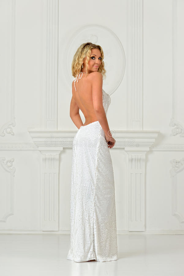 Όμορφη γυναίκα στο προκλητικό μακρύ φόρεμα με τη γυμνή πλάτη. στοκ εικόνες