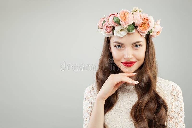 Όμορφη γυναίκα στο στεφάνι θερινών λουλουδιών Όμορφο πρότυπο με τα κόκκινα χείλια makeup και το χαριτωμένο πορτρέτο χαμόγελου στοκ εικόνες
