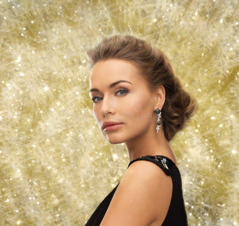 Όμορφη γυναίκα στο φόρεμα βραδιού που φορά τα σκουλαρίκια στοκ εικόνες
