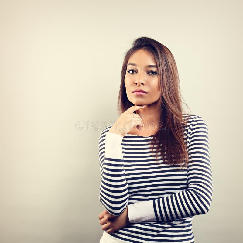 Όμορφη γυναίκα του επιχειρησιακού Λατίνα που σκέφτεται και που φαίνεται σοβαρή επάνω στοκ εικόνα με δικαίωμα ελεύθερης χρήσης