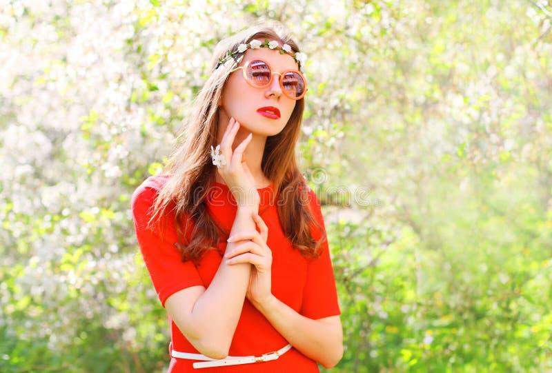 Όμορφη γυναίκα χίπηδων μόδας πέρα από τον ανθίζοντας κήπο στοκ εικόνα