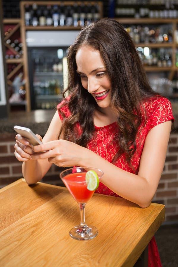 Όμορφη γυναίκα χρησιμοποιώντας το smartphone της και έχοντας ένα κοκτέιλ στοκ εικόνες