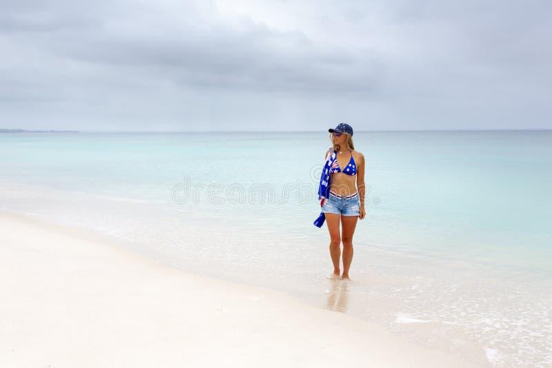 Όμορφη γυναίκα Aussie που περπατά κατά μήκος της άσπρης αμμώδους παραλίας στοκ εικόνες