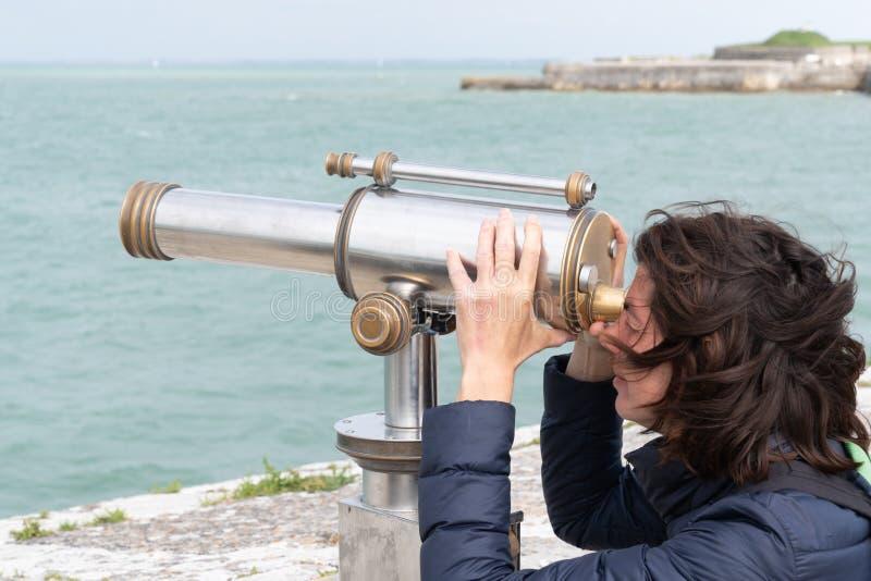 Όμορφη γυναίκα brunette που απολαμβάνεται τη θέα από χρησιμοποιημένη τη νόμισμα παραλία διοπτρών στοκ εικόνες με δικαίωμα ελεύθερης χρήσης