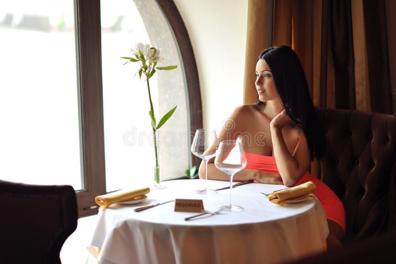 Όμορφη γυναίκα brunette που περιμένει στον πίνακα στο εστιατόριο στοκ εικόνα με δικαίωμα ελεύθερης χρήσης