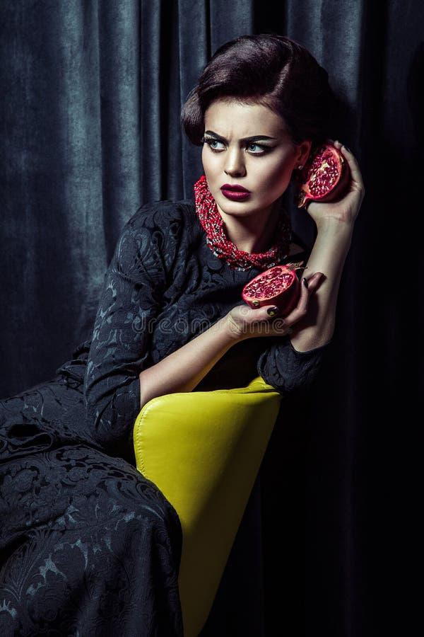 Όμορφη γυναίκα brunette που φορά τη μαύρη τοποθέτηση φορεμάτων βραδιού με δύο ρόδια στα χέρια καθμένος στην κίτρινη καρέκλα στοκ φωτογραφία