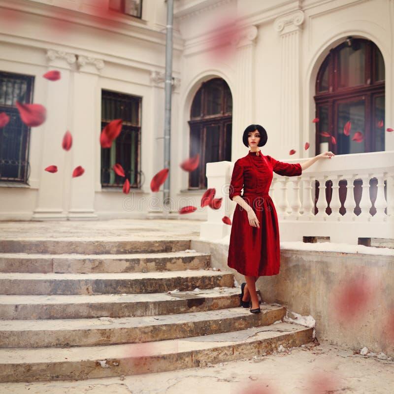 Όμορφη γυναίκα brunette που φορά το κόκκινο φόρεμα, που στέκεται στα σκαλοπάτια στοκ φωτογραφία με δικαίωμα ελεύθερης χρήσης