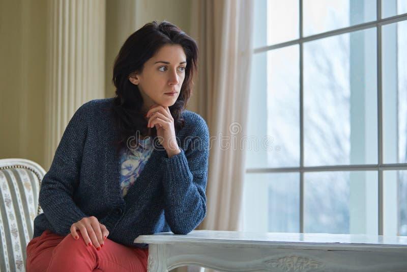 Όμορφη γυναίκα brunette στο διαμέρισμα Λουξεμβούργο στο ξενοδοχείο ή ρετηρέ κοντά στο παράθυρο στοκ εικόνες