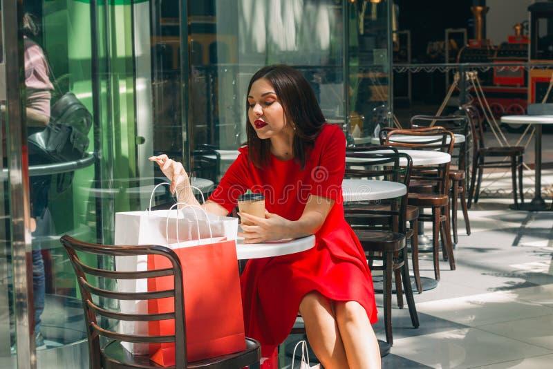 όμορφη γυναίκα brunette στο κόκκινο φόρεμα που εξετάζει τις τσάντες αγορών σε μια καφετερία μετά από να ψωνίσει στη λεωφόρο στοκ φωτογραφία